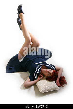 Young Woman Laying in a Classic Pin-up Girl Pose with Her Legs in the Air. - Stock Image