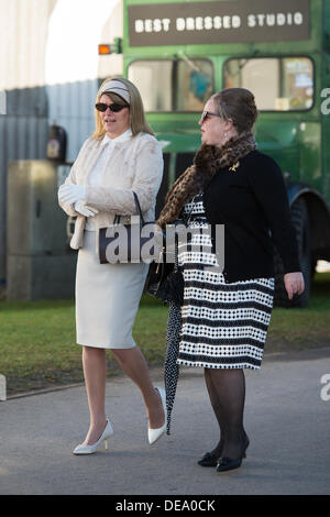 Chichester, West Sussex, UK. 14th Sep, 2013. Goodwood Revival. Goodwood Racing Circuit, West Sussex - Saturday 14th September. Two ladies wearing period clothing walk through the grounds of the circuit. Credit:  MeonStock/Alamy Live News - Stock Image