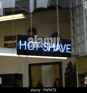 A neon tube sign in a barber shop window advertising a 'Hot Shave' in the UK, Europe - Stock Image