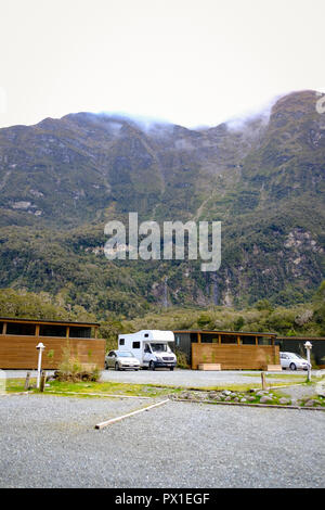 Campervan and car parked at a campsite in Milford Sound, New Zealand - Stock Image