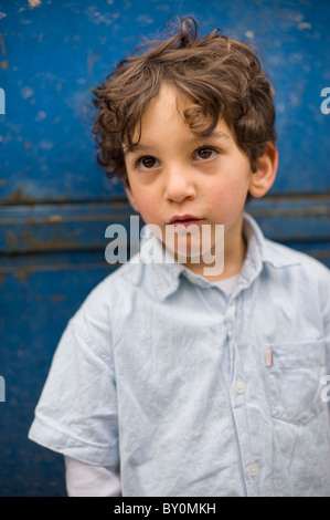 portrait of a young boy in front of a grungy blue background - Stock Image