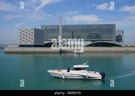 A water taxi in Bahrain Bay, with the Arcapita building and East Park Mosque behind, Manama, Kingdom of Bahrain - Stock Image
