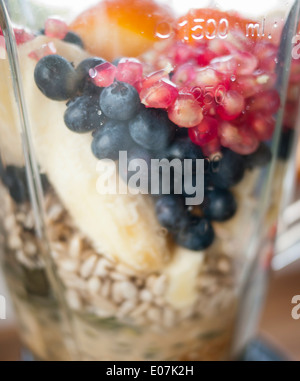 Pomegranate, blueberries, banana and various seeds in a blender in preparation for making a smoothie. - Stock Image