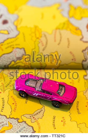 Mattel Hot Wheels violet toy Muscle Speeder car on a page with European map from a opened atlas book on circa June 2019 in Poznan, Poland. - Stock Image