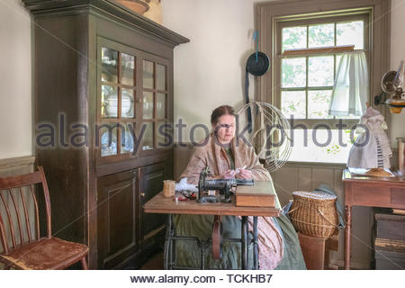 Toronto, Canada-May 30, 2019: The dressmaker woman inside of the McKenzie house. The scene is seen in the Black Creek Pioneer Village which is a famou - Stock Image