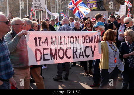 Protestors  with banners, gather outside Parliament to demonstrate against the delays  to Brexit  on the day the UK should have left  the EU - Stock Image