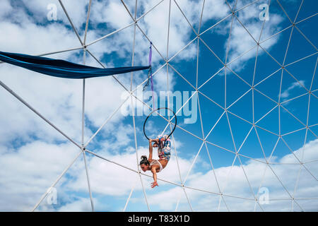 Young fitness perfect body people girl athlete do aerial exercises with a circle - beautiful blue cloudy sky in background - outdoor dangerous sport a - Stock Image