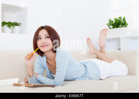 Young woman lying down on front and holding a pencil with smile, - Stock Image