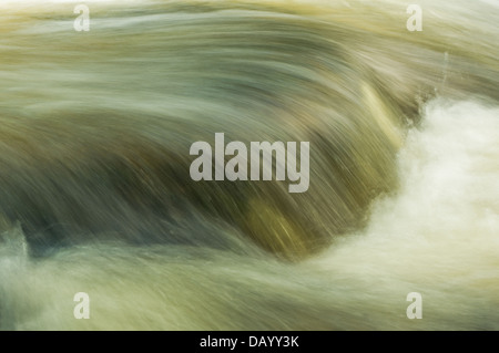 Flecks of dappled evening light upon the racing waters of the River Erme – on part of the 'Town Falls' in Ivybridge, - Stock Image
