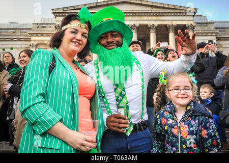 London, UK. 17th Mar, 2019.   A family have enjoyed their day and now enjoy the festivities in the square. Following the spectacular St Patrick's Day Parade earlier, people celebrate and watch performances on Trafalgar Square in the heart of London. Credit: Imageplotter/Alamy Live News - Stock Image
