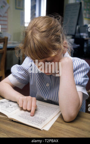 young girl reading in classroom - Stock Image