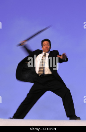 mixed Asian Caucasian business man in motion swinging a stick - Stock Image