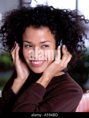Young Woman With Curly Hair Listening To Music - Stock Image