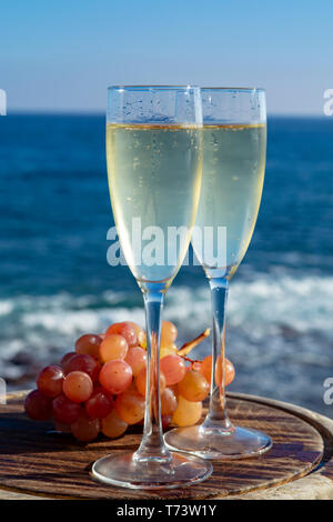 Champagne, prosecco or cava served with pink grape in two glasses on outside terrace with sea view close up - Stock Image