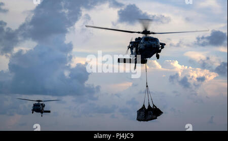 180824-N-FQ836-1193 ATLANTIC OCEAN (Aug. 24, 2018) Two MH-60S Sea Hawk helicopters from the Dusty Dogs of Helicopter Sea Combat Squadron (HSC) 7 transfer supplies from the fast combat support ship USNS Arctic (T-AOE 8) to the Nimitz-class aircraft carrier USS Abraham Lincoln (CVN 72) during an underway replenishment. (U.S. Navy photo by Mass Communication Specialist 3rd Class Jeff Sherman/ Released) - Stock Image
