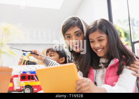 Happy mother and daughter using digital tablet - Stock Image
