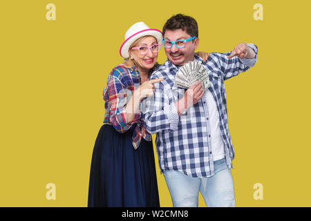 Happy wealthy family, adult man and woman in casual checkered shirt standing pickaback together, holding fan of dollar and pointing finger to money. I - Stock Image