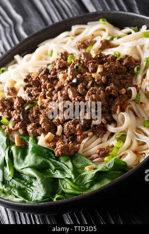 Famous Szechuan style Dan dan noodles is one of the most popular Chinese street foods closeup on the plate on the table. vertical - Stock Image