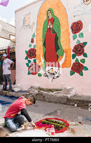 A young boy creates a floral carpet made from colored sawdust and decorated with flowers next to a mural of the Virgin of Guadalupe during the 8th Night Celebration marking the end of the Feast of St Michael in the central Mexican town of Uriangato, Guanajuato. Every year the town decorates 5km of road with religious icons in preparation for the statue of the patron saint to be paraded through the town. Uriangato became an international sensation after wowing Brussels with their floral carpet displayed at the Brussels Grand-Place during the Belgium Floral Carpet festival. - Stock Image