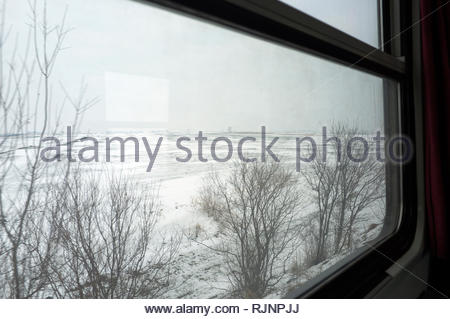 Serbian train journey during winter - travelling across the Pannonian Plains in the province of Vojvodina, Serbia. - Stock Image