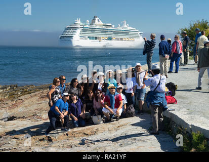 Asian tourists taking a group picture with a cruise ship in the background,  Bar Harbor, Maine, USA. - Stock Image