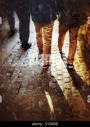 Unknown men walking along an alley - Stock Image