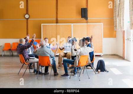 Men praying with arms raised in prayer group in community center - Stock Image