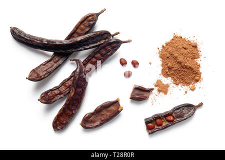 Carob bean pods, seeds and powder on white background - Stock Image