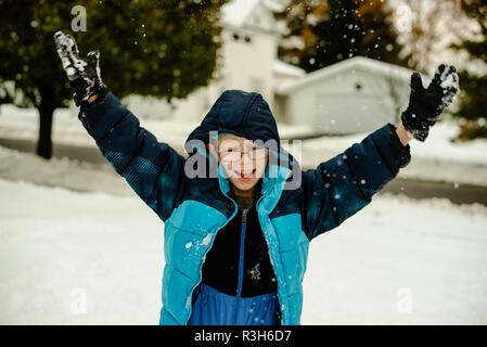 12-year old boy throws snow up in in the air on a winter day in November in the United States. - Stock Image