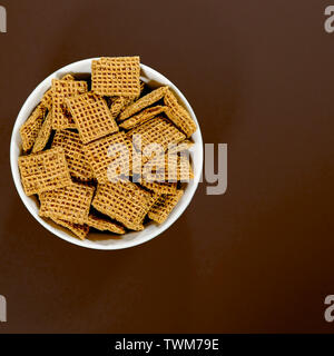 Bowl of Wholegrain Shreddies Breakfast Cereals Against a Brown Background With No People - Stock Image
