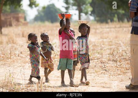 Kisambo Village, Yako, Burkina Faso, 28th November 2016; children bringing shelled ground nuts to women working in the village garden. - Stock Image