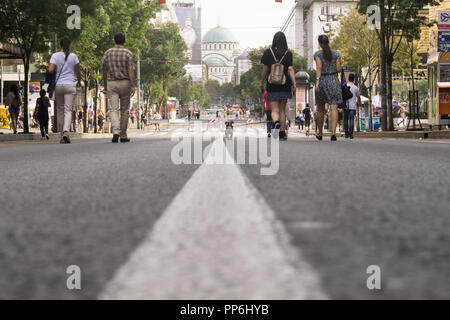 Low angle view of people walking along the central Belgrade street Srpskih Vladara, turned into a pedestrain street for a day. - Stock Image