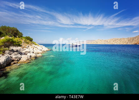 Lagoon in Hydra island, Greece. Crystal clear turquoise water. Luxury yacht with mooring ropes against the rocks. - Stock Image
