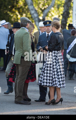 Chichester, West Sussex, UK. 14th Sep, 2013. Goodwood Revival. Goodwood Racing Circuit, West Sussex - Saturday 14th September. A group of visitors, dressed in period clothing, including one man in an RAF uniform and a lady in a long dog check skirt shortly after entering. Credit:  MeonStock/Alamy Live News - Stock Image