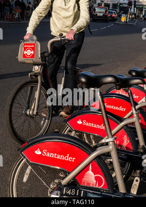 TFL Santander sponsored London red rental hire bikes in Southwark Street with male cyclist starting his hire ride from the bike terminal docking station. Transport for London Southwark London UK - Stock Image