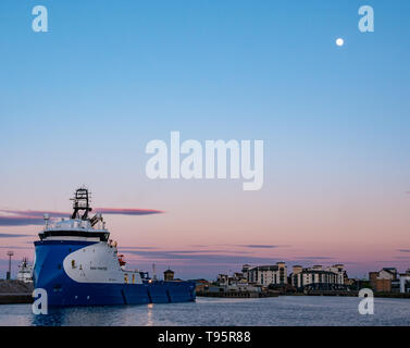 Leith Docks, Edinburgh, Scotland, United Kingdom, 16th May 2019. UK Weather: A glorious sunny day comes to an end over the harbour area in Leith with a ship in the harbour lit up by the last rays of the sun with a nearly full bright moon above. Credit: Sally Anderson/Alamy Live News - Stock Image