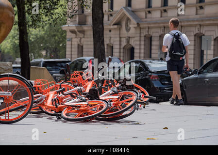 A young white male person with a backpack or daypack walks down Loftus Street in Sydney Australia past a collection of hire bikes fallen on the ground - Stock Image
