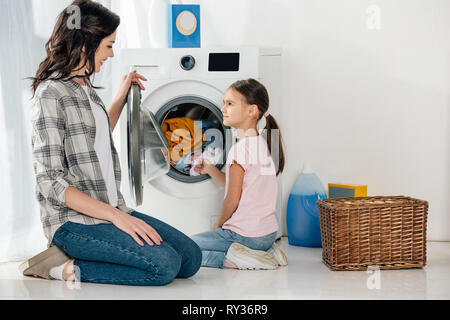daughter in pink t-shirt and mother in grey shirt sitting on floor near washer with clothes in laundry room - Stock Image