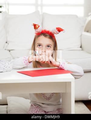 Girl Wearing Santa Headband With Pencil And Cardpaper - Stock Image