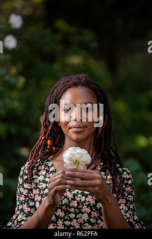 Closeup of a woman holding a flower in a garden - Stock Image