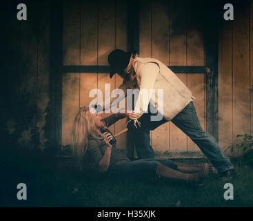 A scary dangerous man with a mask is attacking a woman outside in the night for a fear, murder or victim concept. - Stock Image