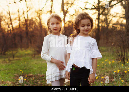Stylish portrait of sisters in spring meadow. Girls posing in white dresses. Family photo - Stock Image