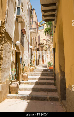 Italy Sicily Agrigento old town steep narrow streets scene stone steps stairs plants planters cactus cacti houses balconies drainpipe - Stock Image