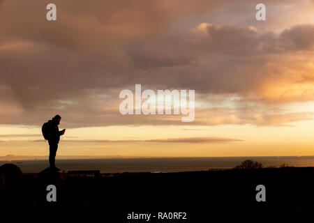 On top of the world - a back packer checks directions on a mountain in Scotland - Stock Image