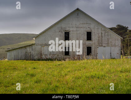Old barn of the historic Pierce Point Ranch in Point Reyes National Seashore, on a blue cloudless ky. This ranch on Tomales Point (aka Pierce Point) i - Stock Image