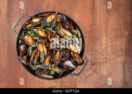 Marinara mussels, mules mariniere, in a braizer, overhead view - Stock Image