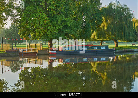 Stratford upon Avon and early morning autumn reflections on the River Avon with a narrow boat moored at the old chain ferry crossing. - Stock Image