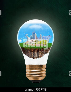 Floating city inside light bulb with renewable energy symbols of wind turbines and solar panels. Concept of eco-friendly, energy efficient city and id - Stock Image