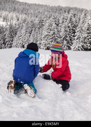 small boy and girl  playing in the snow with wooded winter  mountain landscape behind - Stock Image