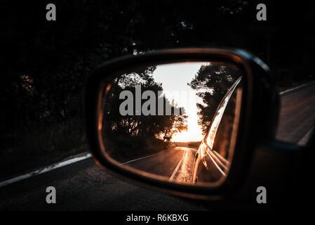 Amazing orange summer sunset reflected in side mirror. Summer travel - Stock Image